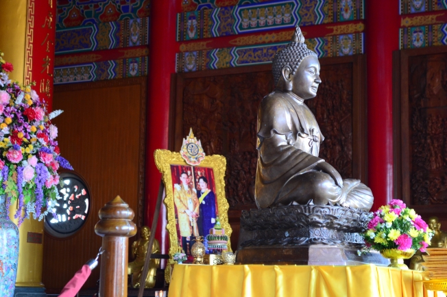 Buddha and a framed photo of the King and Queen